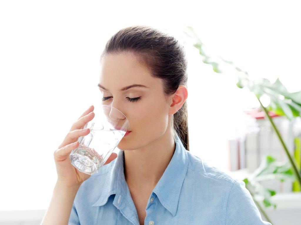 žena koja pije vodu iz čaše