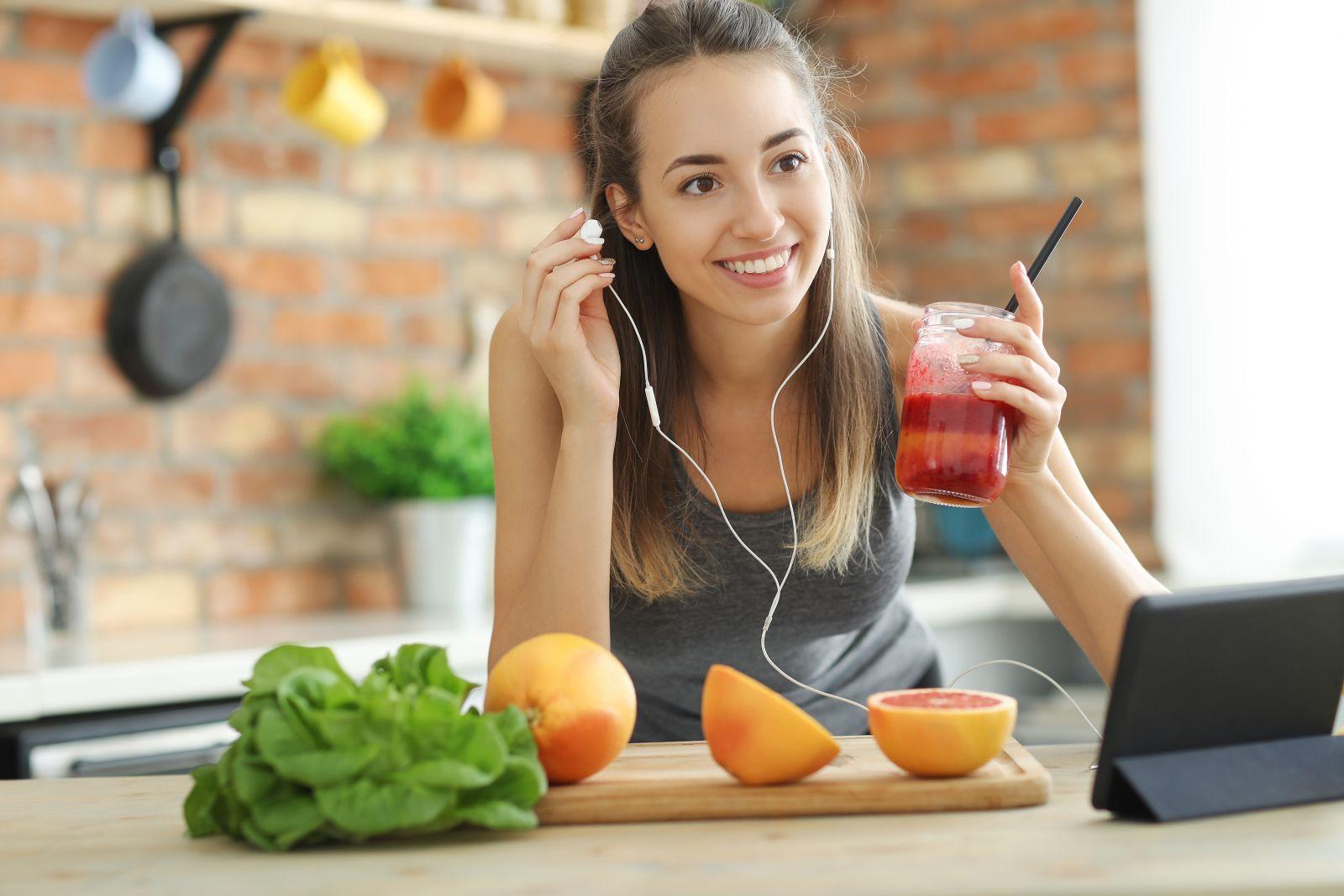 devojka drži smuti u ruci, a na stalu ispred nje se nalazi voće