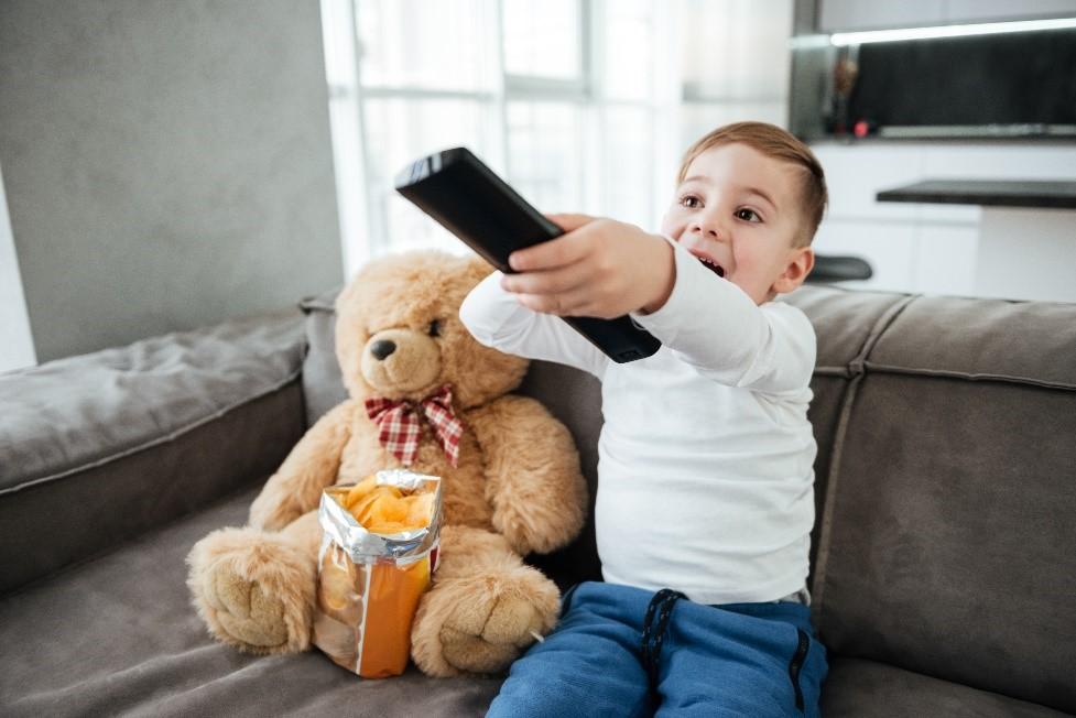 dečak sedi na kauču sa daljinskim upravljačem u rukama