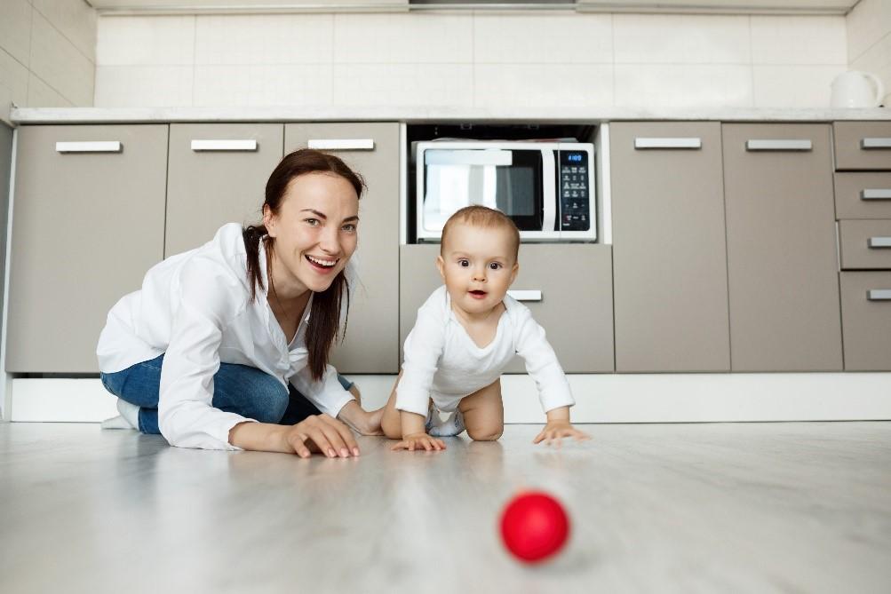 mama na podu pored bebe koja puzi ka loptici