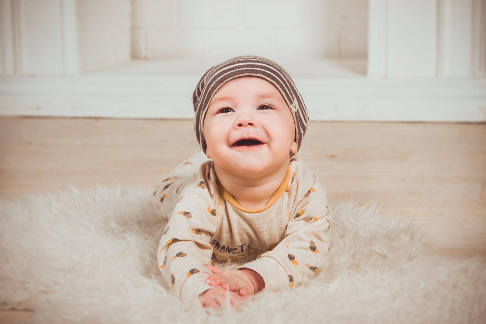 nasmejana beba leži na podu