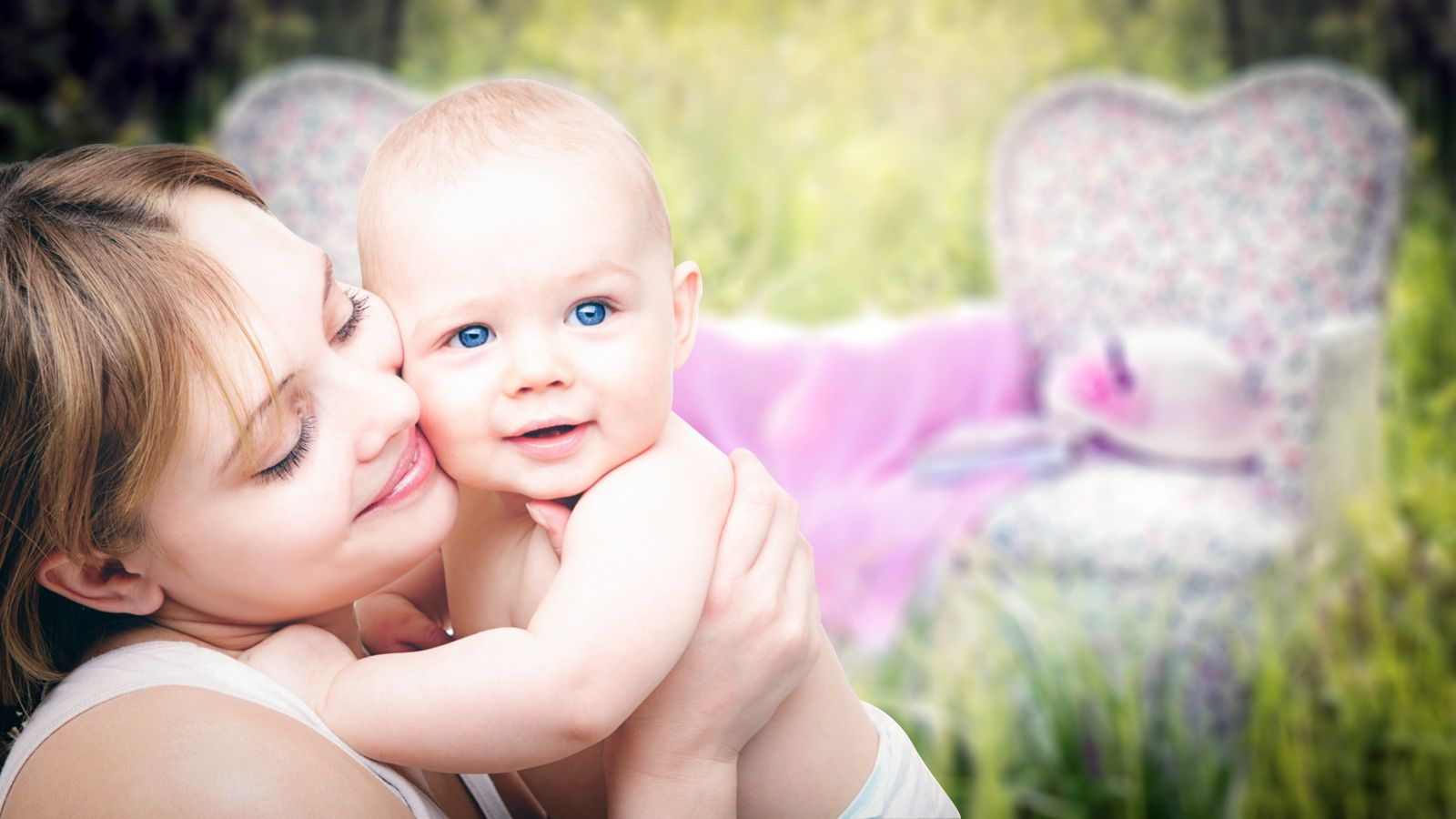 nasmejana majka drži bebu u naručju dok sedi u prirodi