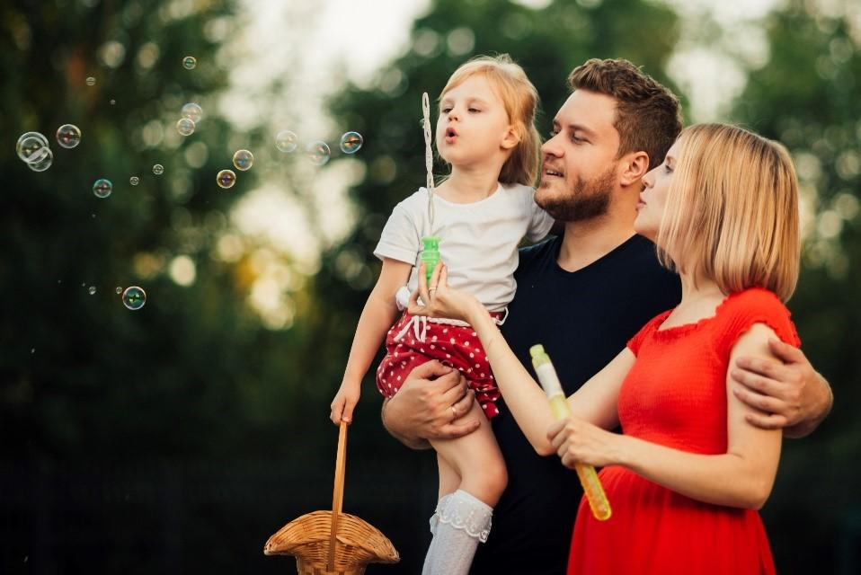 mama,tata i ćerka zagrljeni prave balončiće od sapunice