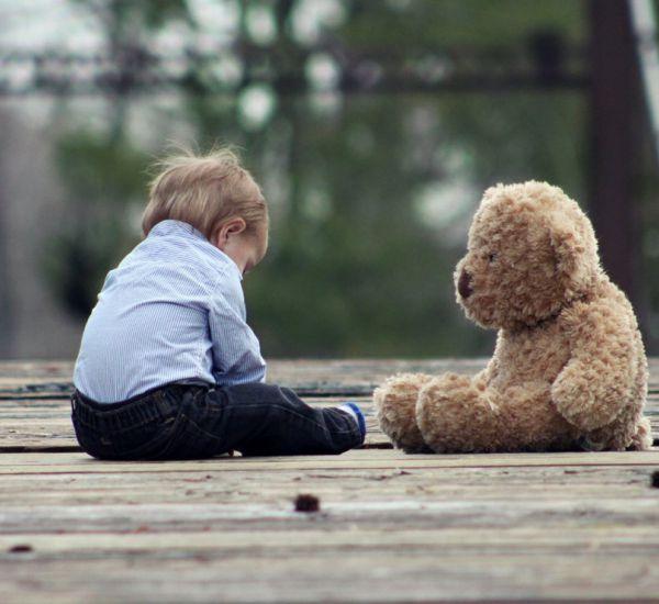 dečak sedi pored plišanog mede