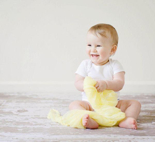 nasmejano dete sedi na podu