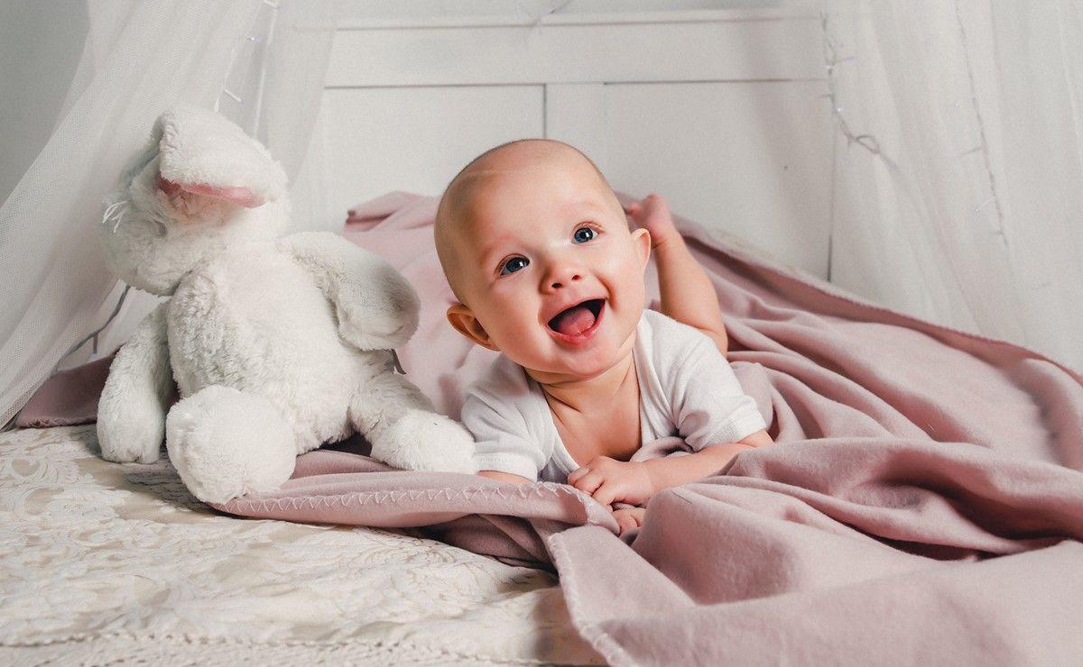 nasmejana beba leži na krevetu pored plišanog mede