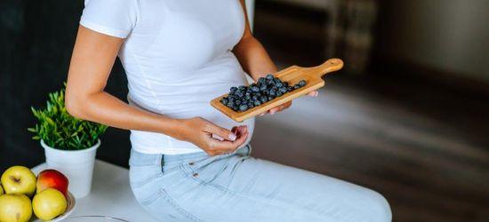 trudnice naslonjena na kuhinjsku radnu ploču drži dasku sa maslinama