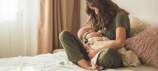 majka sedi na krevetu i u naručju drži bebu koju doji