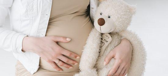 trudnica koja jednu ruku drži na stomaku a u drugoj drži plišanog medu